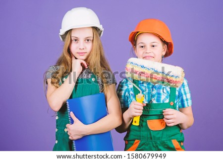 Kids choosing paint colour for their new room. Kids girls planning renovation. Children sisters run renovation their room. Amateur renovation. Sisters renovating home. Home improvement activities.