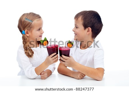 Kids clinking with fresh beetroot and carrot juice - healthy diet - stock photo