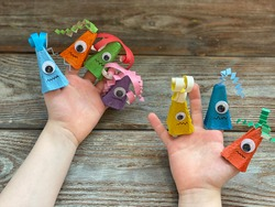 Kids Craft, a fun monster with one eye made out of an egg box and colored paper, is dressed on children's fingers.