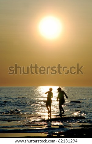Kids dancing in reflection of sunlight. two silhouetted kids dance in sparkling \