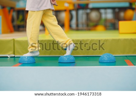Kids doing massage hedgehog for foot legs exercises in gym at kindergarten or elementary school. Children sport and fitness concept. Stock foto ©