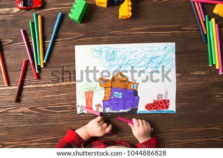 Kids drawing and a lot of painting tools  on a wooden background