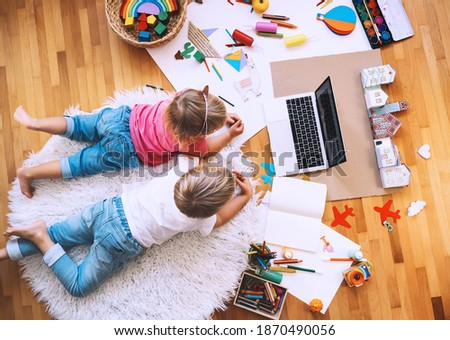 Kids drawing and making crafts with online art classes at home. Children using laptop to distance online education. Background for preschool, kindergarten or family daycare. Childcare and technology.