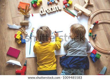 Kids drawing on floor on paper. Preschool boy and girl play on floor with educational toys - blocks, train, railroad, plane. Toys for preschool and kindergarten. Children at  home or daycare. Top view #1009485583