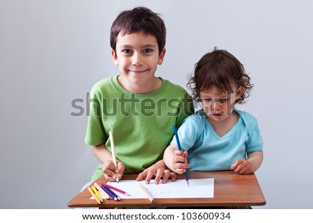 Kids drawing together - preschool boy helping his toddler brother