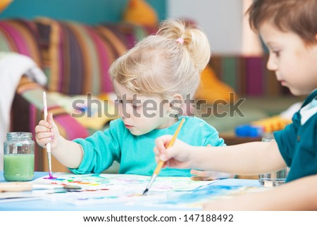 Kids drawing with watercolor paints
