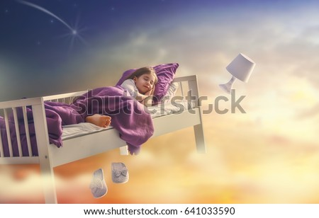 Kids dreams. Cute child girl is flying in her bed trough star sky.