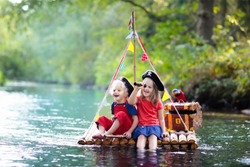 Kids dressed in pirate costumes and hats with treasure chest, spyglasses, and swords playing on wooden raft sailing in a river on hot summer day. Pirates role game for children.