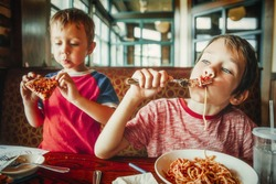 kids eat pizza and pasta at cafe. children eating unhealthy food indoors