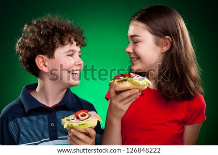 Kids eating healthy sandwiches on green background