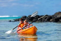 Kids enjoying paddling in colorful red kayak at tropical ocean water during summer vacation