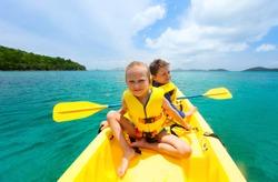 Kids enjoying paddling in colorful yellow kayak at tropical ocean water during summer vacation