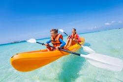 Kids enjoying paddling in orange kayak at tropical ocean water during summer vacation