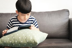 Kids faith in God - An adorable asian little boy concentration reading holy bible by himself on a sofa. Message, Faith, Foundation, Quiet time, Wisdom, Child, Jesus love me, Sunday school, Lockdown.