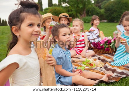 Kids fashion concept. The group of teen boys and girls sitting at green grass at park. Children colorful clothes, lifestyle, trendy colors concepts. #1110293714