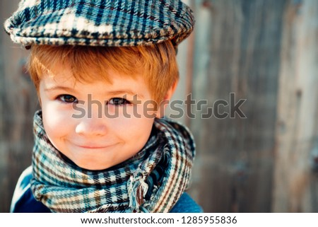 Kids fashion. The boy in a vintage cap. Old school. Smiling child. Beautiful poster on wooden background.