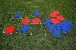 Kids festival . Children play chess . Giant Noughts and Crosses green backgrounds .