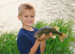 Kids fishing - a cute boy smiles as he holds a big fish he caught