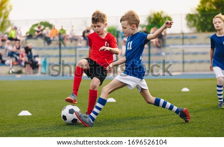 Kids Football Players Kicking Ball on Soccer Field. Sports Soccer Horizontal Background. Spectators on Stadium in the Background. Youth Junior Athletes in Red and Blue Soccer Shirts. Sports Education