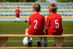 Kids Football Team. Two Young Boys Watching Soccer Match. Football Tournament Competition in the Background. Children Football Team Players in Red Jersey  Uniforms on The Soccer Stadium
