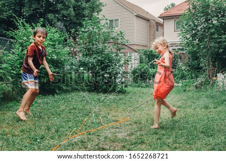 Kids friends boy and girl splashing with gardening hose on backyard on summer day. Children playing with water outside at home yard. Candid authentic real life moment of funny family activity.