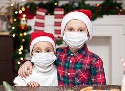 Kids girl and boy in Santa caps in medical masks congratulate each other Merry Christmas and Happy New Year and hug.