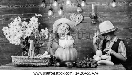Kids girl boy wear hat celebrate harvest festival rustic style. Celebrate fall traditions. Elementary school fall festival idea. Autumn harvest festival. Children play vegetables pumpkin cabbage.