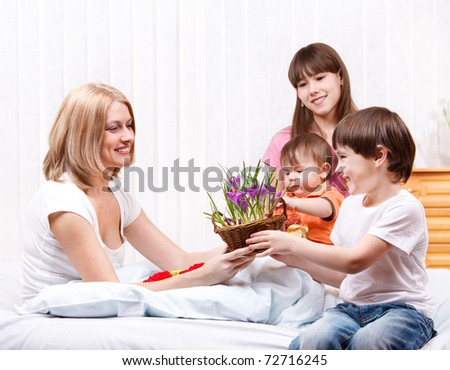 Kids greeting mom with Mother's Day - stock photo