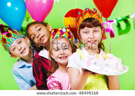 Kids group in party crowns holding birthday cake