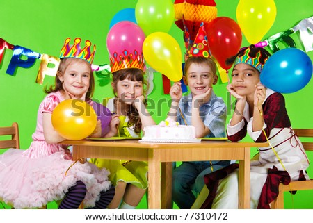 Kids group sitting at the table with the birthday cake