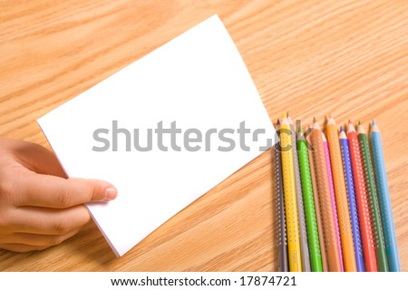 Kids hand holding blank paper for message. Copy space