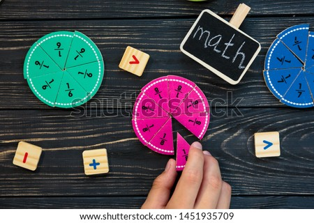 Kids hand moves colorful math fractions on dark wooden background or table. Interesting creative funny math for kids. Education, back to school concept. Geometry and mathematics materials.