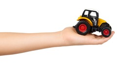 Kids hand with yellow plastic traktor toy. Farming vehicle, harvest equipment. Isolated on white background.