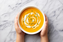 Kids hands holding a bowl with pumpkin soup. Marble background. Top view.