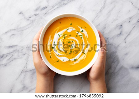 Kids hands holding a bowl with pumpkin soup. Marble background. Top view. Сток-фото ©