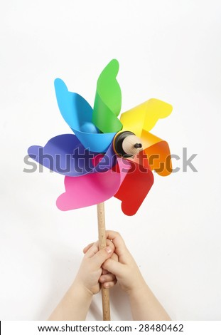 Kids hands holding a windmill with lots of color an a white background.