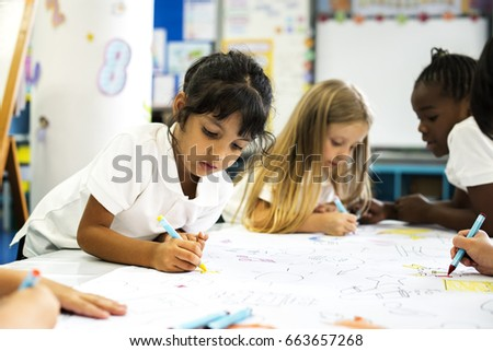 Kids hands holding colored pencils painting on art drawing paper