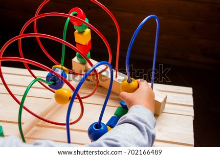 kids hands playing Wooden Wire Maze Educational Game Toy toddler blocks. learning color and form in various shapes. Develops fine motor skills and logical thinking.creative baby #702166489