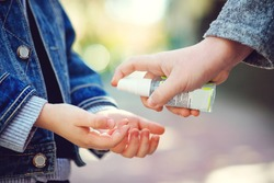 Kids hands using sanitizer gel, closeup. Children disinfecting hands with antiseptic gel. Coronavirus epidemic. Coronavirus quarantine. Sanitizer for prevent spread of germs, bacteria, coronavirus