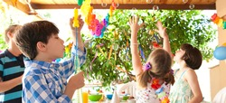 Kids having fun enjoying a colorful birthday party in a home garden, blowing and catching bubbles, outdoors. Kid celebrating occasion in bright house exterior. Children fun activities, sunny day.