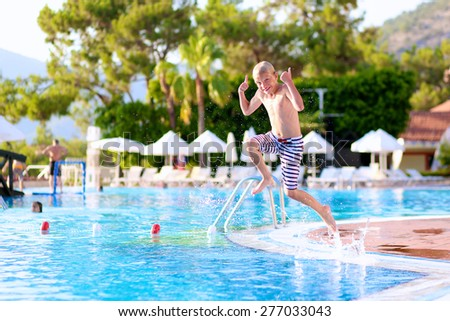 Kids having fun in summer. Happy active child, blonde caucasian teenage boy, jumping and diving into swimming pool in tropical resort at sunset - summertime vacation concept