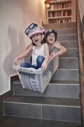 Kids having fun sledding down stairs in a storage box