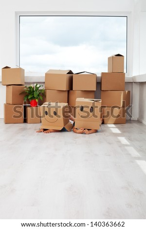 Kids having fun while moving in a new home - laying with cardboard boxes
