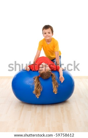 Kids having fun with a large exercise ball helping each other - isolated