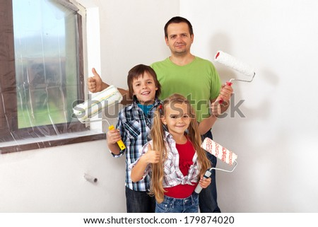 Kids helping there father painting- holding paint rollers