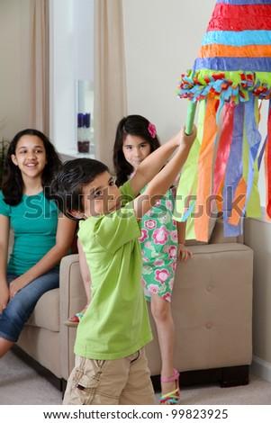 Kids hitting a pinata at birthday party