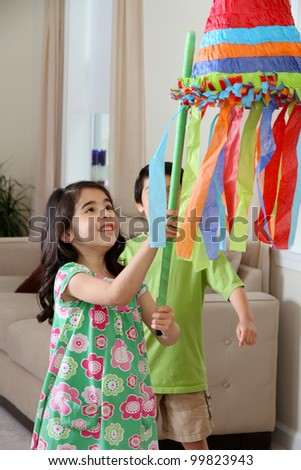 Kids hitting a pinata at birthday party