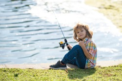 Kids hobby. Smiling child fishing on the lake. Boy with spinner at river. Portrait of excited boy fishing. Boy at jetty with rod