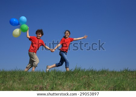 Kids holding balloons running outdoor