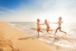 Kids holding hands and running along sandy beach